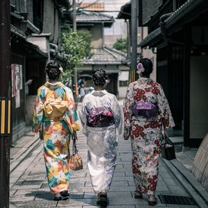 three-geisha-walking-between-buildings-1325837